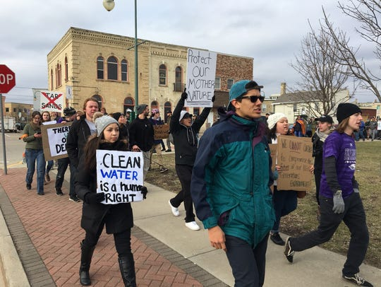 Protesters march through downtown Whitewater, chanting