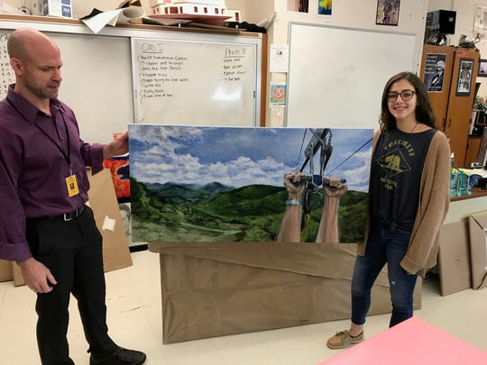 Haley Florio and her art teacher, Maurice Johnson, at Butler High School. The senior recently won an art scholarship for her painting.
