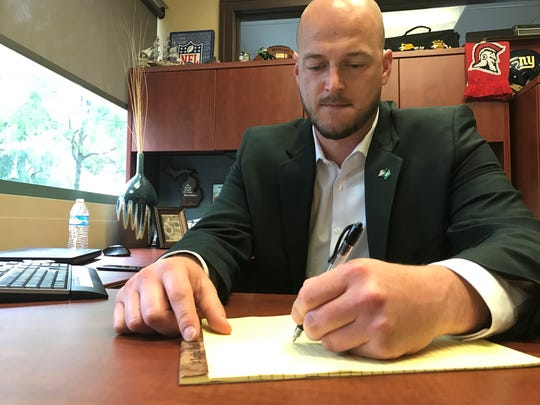 "Former Michigan State QB Ryan Van Dyke sits at his desk in Northville, drawing up the game-winning play in 2001 against Notre Dame. The play was called ""93-X-Cross."" All-American wide receiver Charles Rogers was the ""X,"" turning a quick slant into a 47-yard touchdown pass to  seal a 17-10 victory in South Bend."