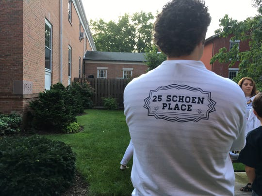Shirts are given outside a Village Board meeting Aug. 15, 2017, to those supporting development on Schoen Place.