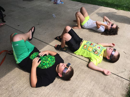 From left, Ethan Weis, 10, of Fremont, and Ty, 7, and Ella Schadwill, 9, of Vickery use special glasses to view the partial solar eclipse in Clyde.