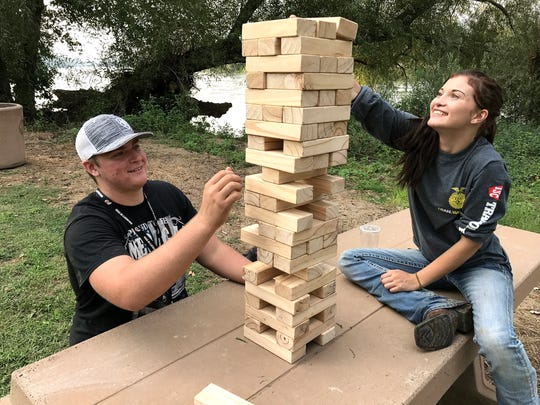 Tyler Bassinger, left, and Kelley Bettendorf play a jumbo version of Jenga during Saturday's food truck event at Anderson River Park.