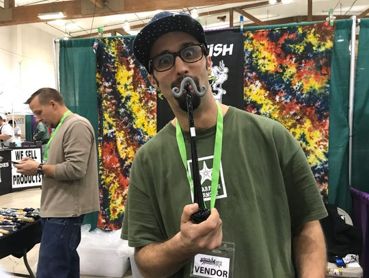 "A vendor representative of Starfish Designs holds one of the ""Original Gandolf"" mustache pieces designed by Andy Eggleston at a previous Hemp and Cannabis Fair at the Oregon State Fairgrounds and Exposition Center. The event returns April 14-15."