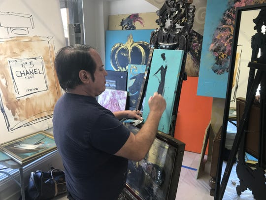 San Antonio-based artist Franco Mondini-Ruiz creates pop-up art at Casa Authentique Tuesday. The visiting artist is selling his artistic portraits and landscapes to customers, as well as making custom works for them, Wednesday and Thursday.