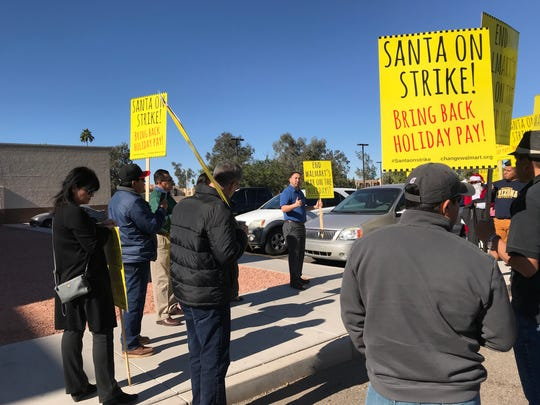 Protesters gather around Arizona state Sen. Martin Quezada, who speaks about Walmart's holiday-pay policy on Dec. 7, 2017.
