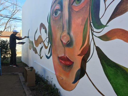 Rolando Diaz paints a mural at FaithWorks.