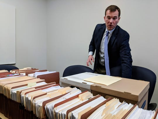 Michigan's marijuana lead regulator Andrew Brisbo shows off the files from a single license application for medical marijuana in 2018. Brisbo will lead the new Marijuana Regulatory Agency.