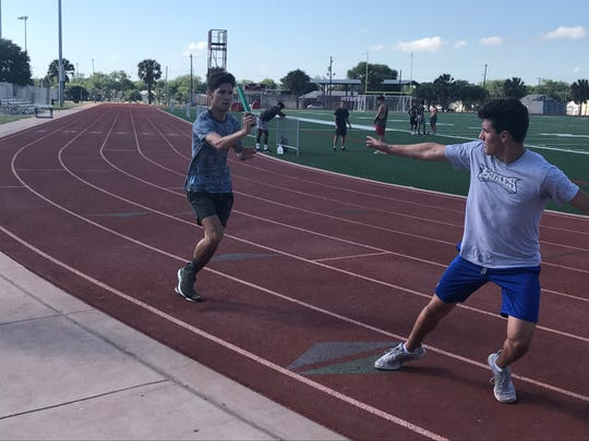 Ray's Michael Vazquez and Jarrett Garza work on exchanges during practice Wednesday, May 9 in preparation for the UIL State Track & Field Championships this week.