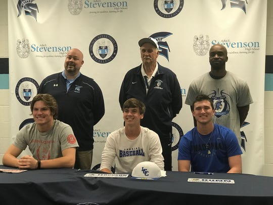 Livonia Stevenson seniors Parker Graham, George Ferguson and Devin Dunn celebrate their college futures while tipping their caps to their high school careers. Standing behind the players are Stevenson football coach Randy Micallef, baseball coach Rick Berryman and basketball coach Kareem Smart.