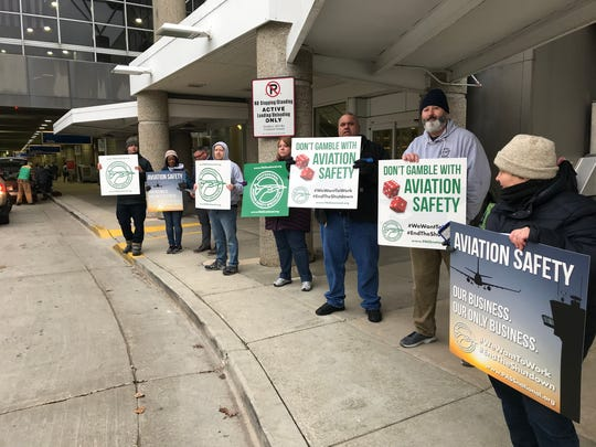 Federal workers protest the government shutdown outside General Mitchell Airport in Milwaukee on Saturday.