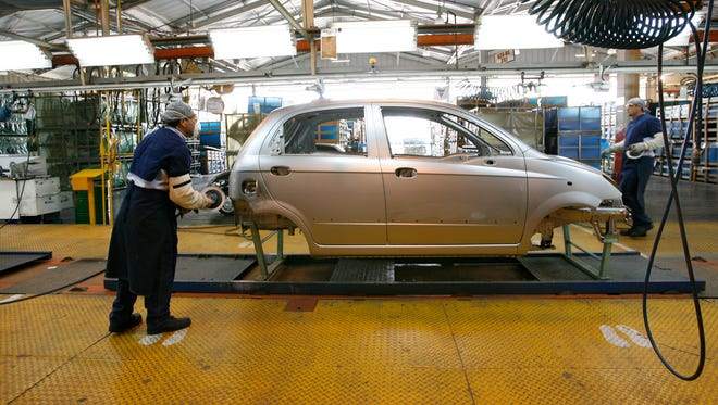 Workers adding body components to a Chevy Spark on the assembly line at the General Motors assembly plant in Valencia, Venezuela.
