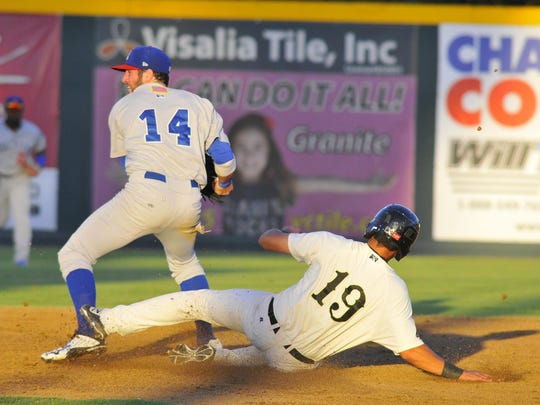 Visalia Rawhide's Joe Munoz, 19, slides into second base as he gets tagged out by the Stockton Ports' Mikey White III on Thursday at Recreation Park.