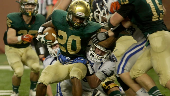Muskegon Catholic Central's  #20 LaTommy Scott is stopped for a short gain by Waterford Our Lady of the Lakes Mclane Burtum at the MHSAA Division 8 state football championships at Ford Field in Detroit, Nov. 27, 2015.