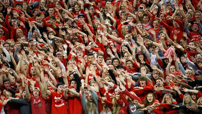 Romeo fan zone wave their hands in the air as they cheer for their team, during the Michigan High School Athletic Association football Division 1 finals  against Detroit Cass Tech at Ford Field in Detroit on Saturday, Nov. 28, 2015.
