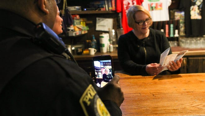 University of Iowa Police Officer Alton Poole live streams video from his phone as Iowa City Police Officer Ashten Hayes and Coralville Police Officer Juan Coleman visit Deadwood on Wednesday, Feb. 24, 2016. The three spent part of their afternoon recruiting teams from local businesses for the upcoming Iowa City Polar Plunge to benefit Special Olympics Iowa.