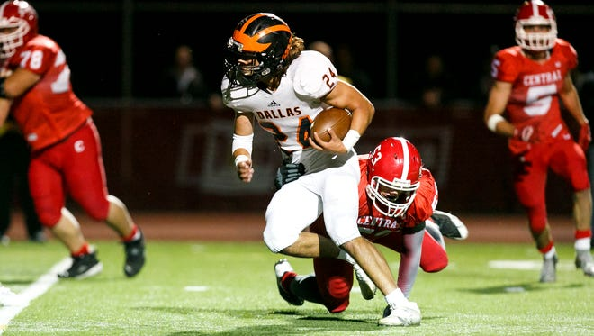 Dallas' Tanner Earhart (24) tries to break a tackle from Central's Sam Crow (53) at a game on Friday, Sept. 30, 2016, at Central High School in Independence. Central won the game 21-20.