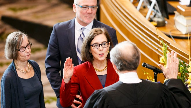 Gov. Kate Brown is sworn in by Chief Justice Thomas A. Balmer on Monday, Jan. 9, 2017, at the Oregon State Capitol. The governor was accompanied by her husband, First Gentleman Dan Little, and her mother, Sally Brown.