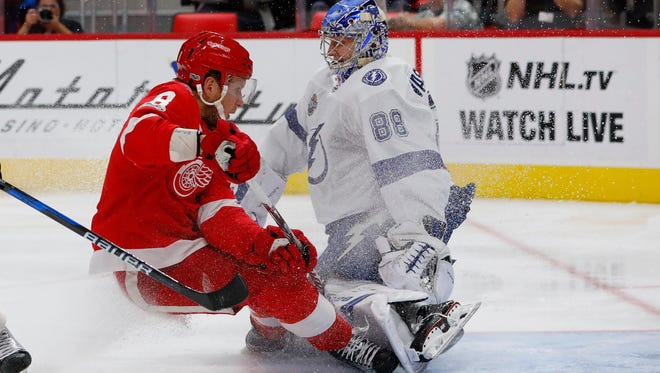 Red Wings left wing Justin Abdelkader (8) collides with Lightning goalie Andrei Vasilevskiy (88) in the second period on Monday, Oct. 16, 2017, at Little Caesars Arena.