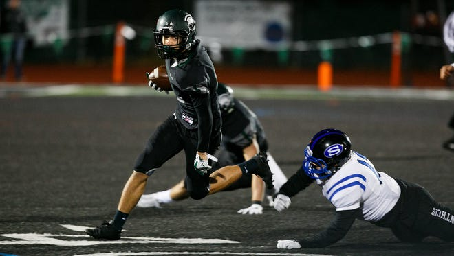 West Salem's Anthony Gould (15) dodges a tackle in a OSAA 6A quarterfinal game against South Medford on Friday, Nov. 17, 2017, at West Salem High School.