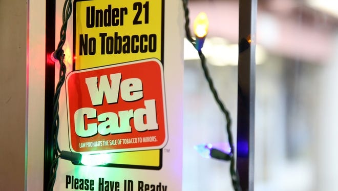 A sign on the door displays the upcoming state law age requirement at Pat's Cigs in Keizer on Thursday, Dec. 28, 2017. A new law that bans selling tobacco products to anyone under 21 takes effect Jan. 1, 2018.