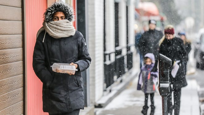 Ashanti Watts carries food in Broad Ripple Village as snow falls in Indianapolis.