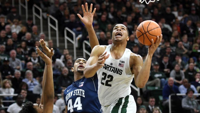 Michigan State's Miles Bridges, right, scores between Penn State's Josh Reaves, left, and Julian Moore during the second half on Wednesday, Jan. 31, 2018, at the Breslin Center in East Lansing. The Spartans won 76-68.