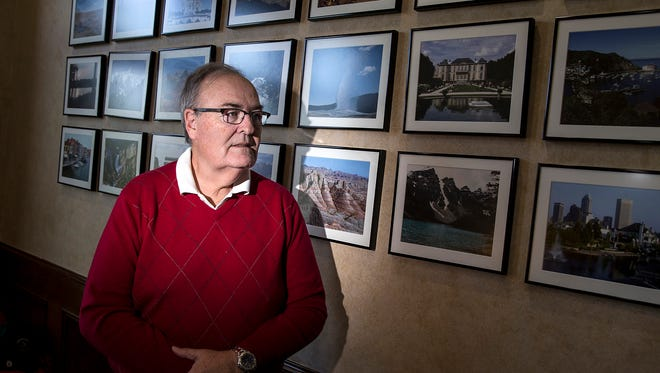 Rich Bell is a retired lawyer who has filed or threatened hundreds of copyright infringement lawsuits over a photo he shot of the Indianapolis skyline in 2000, pictured at bottom right. Bell poses for a portrait against a wall of pictures he has taken, at his home in McCordsville, Ind., Thursday, April 26, 2018.