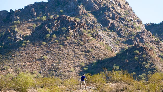 A hiker makes his way up Trail 100 at Dreamy Draw Recreation Area in Phoenix on Wednesday, Oct. 14, 2015, on a day that saw the Valley tie a heat record with a high of 100 degrees.