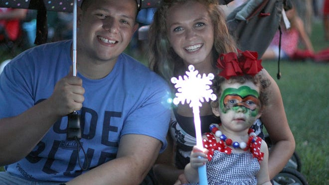 Rain moved in as the Hacketts, Houston, Morgan and 2-year-old Heidi, wait for the fireworks in Gallatin on Saturday.