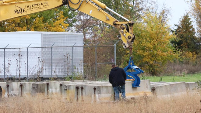 A worker for Eppel Construction checks grip of a crane on a concrete block, typically used for traffic control, just south of Prairie Central Co-op elevator at Ocoya Wednesday morning.