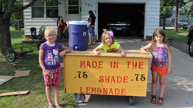 Friends (from left) Kalista Billig, Skyler Gillitzer and Kyra Schmitt stand next to their lemonade stand Friday in Richmond. The friends painted the stand, which made an appearance at Richmond River Lakes Days.