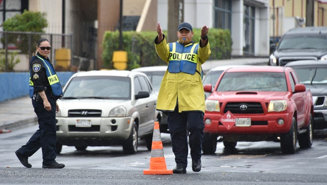 Guam Police Department Officer Morgan Reyes and officer trainee Keith A. Aguero control traffic at the intersection of Route 16 and Harmon Loop Road in Dededo, as Tropical Storm Maria moves away from Guam on July 5, 2018.