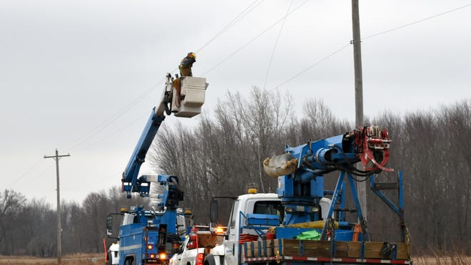CE crews repair a downed power line Sunday on Orland Road in Bronson Township.