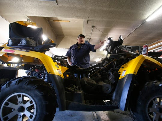 Dustin Lauritsen, a technician with Dusenbery Inc., talks Monday about an all-terrain vehicle he is repairing at his garage in Aztec.