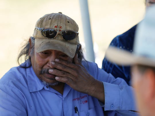 Earl Yazzie wipes away tears while talking to U.S. Sen. Tom Udall about the effects the Gold King Mine spill had on his farm during a meeting Friday at his home in Shiprock.