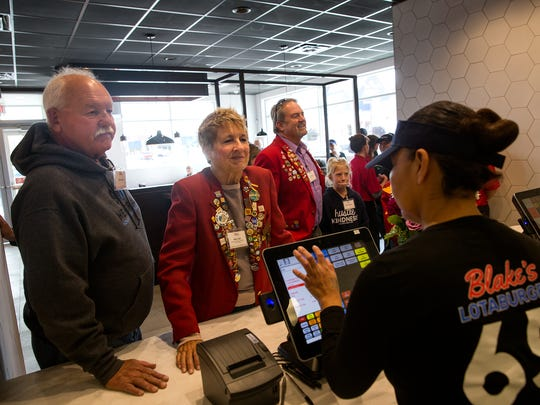 Eric Lien, left, and Kim Lien give their order to Blake's Lotaburger crew member Karen Nelson Thursday at the chain's new Farmington location.