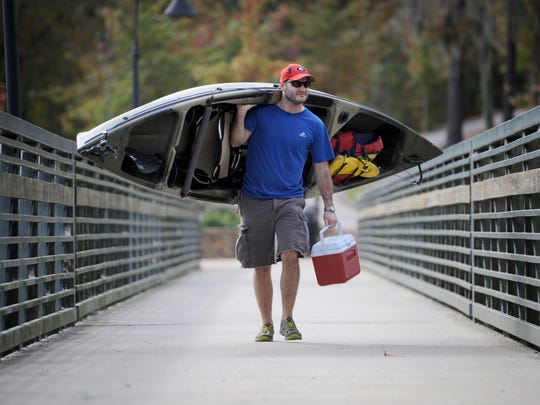 Brett DeLoach carries his kayak on a bridge spanning