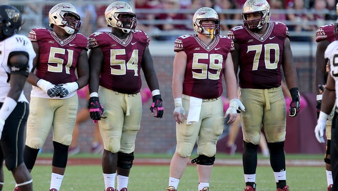 Members of the offensive line, from left to right, offensive tackle Bobby Hart (51), guard Tre' Jackson (54), center Ryan Hoefeld (59) and guard Josue Matias (70), take a break between plays as Florida State cruises past the Wake Forest Demon Deacons on Saturday Oct., 4, 2014 at Doak Campbell Stadium.
