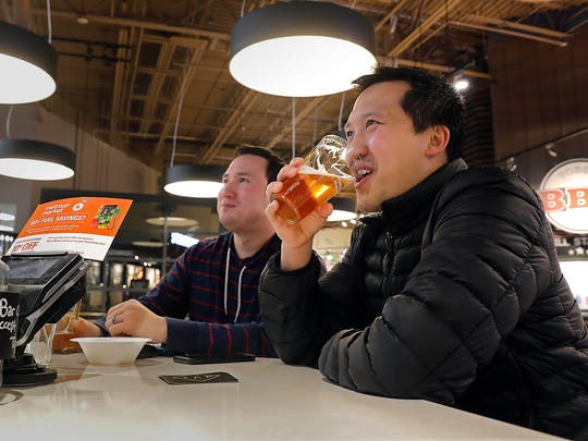 Frank Savel, left, and Lue Yang, both from Wauwatosa, enjoy a draft brew while watching television at Metro Market, 6950 W. State St., in Wauwatosa.