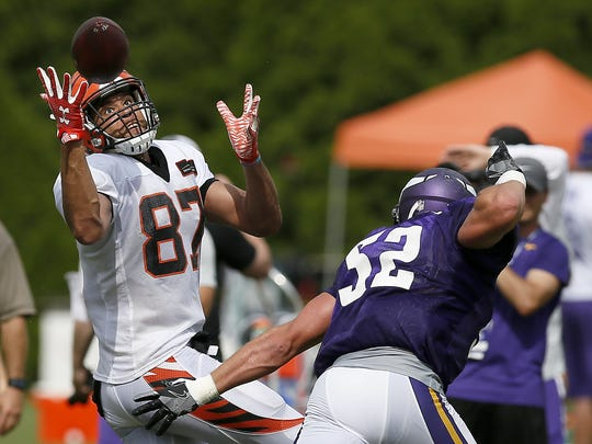 Cincinnati Bengals tight end C.J. Uzomah (87) pulls in a bobbles pass over the head of Minnesota Vikings outside linebacker Chad Greenway (52) during practice on Day 13 of training camp at the Paul Brown Stadium practice facility in downtown Cincinnati on Wednesday, Aug. 10, 2016. The Bengals and Vikings met on the practice field for the first of two joint practices ahead the first pre-season game of the year.