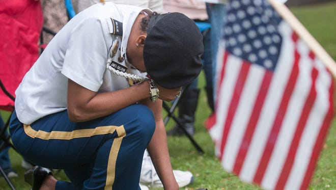 "U.S. Army veteran Inga Yna Jones-Sullivan of Bear, DE, reflects as ""Taps"" is performed during Vineland's Memorial Day Service held at Landis Park on Monday.  05.29.17"