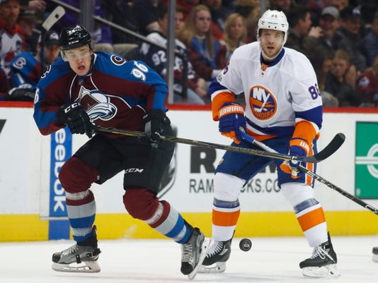 Colorado Avalanche right wing Mikko Rantanen, front, of Finland, reaches out for the puck as New York Islanders left wing Nikolay Kulemin, of Russia, defends in the second period of an NHL hockey game Friday, Jan. 6, 2017, in Denver. (AP Photo/David Zalubowski)