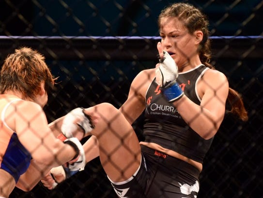 In this file photo, Brogan Walker lands a front thrust kick to the midsection of Emiko Raika in a 125-pound fight at PXC 50 at the UOG Calvo Field House.