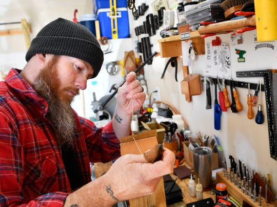Jonathon Long hand stitches a wallet in his workshop