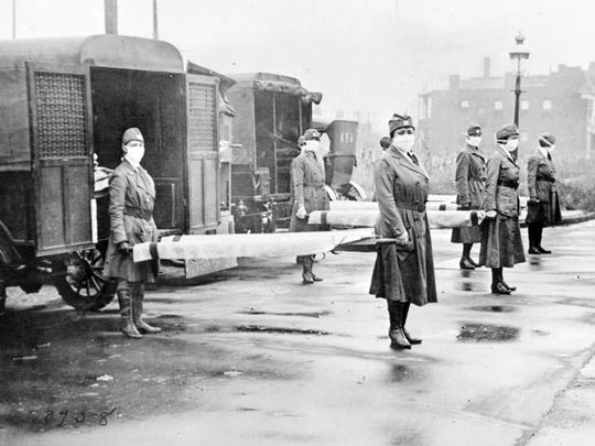 St. Louis Red Cross Motor Corps personnel wear masks in Oct. 1918 as they hold stretchers next to ambulances in preparation for victims of the Spanish flu epidemic.