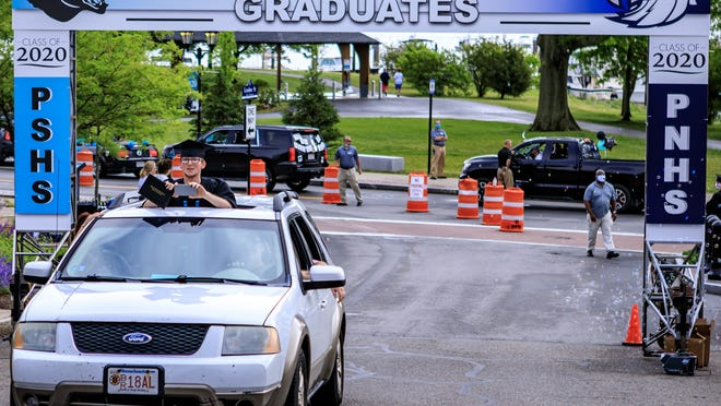 Ryan Brown rides up Leyden Street displaying his diploma after graduating from Plymouth South High School on Jun 6, 2020.
