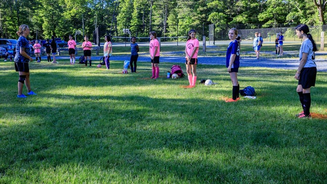Maintaining proper social distancing, Cordage Soccer Club players begin practice Thursday at the Hedges Pond field.