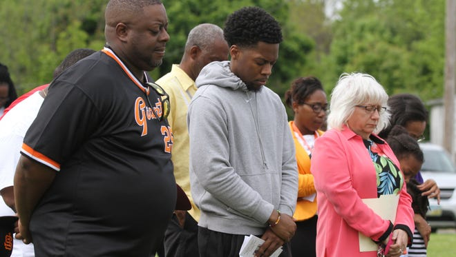 Participants of a rally for Mothers United to Save at Oasis bow their heads during a prayer at Oasis of Love Park on Friday afternoon. The event highlighted those who were gunned down in an act of violence.