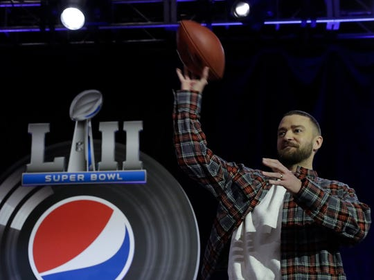Justin Timberlake holds a football during a news conference for the NFL Super Bowl 52 football game halftime show Thursday, Feb. 1, 2018, in Minneapolis.
