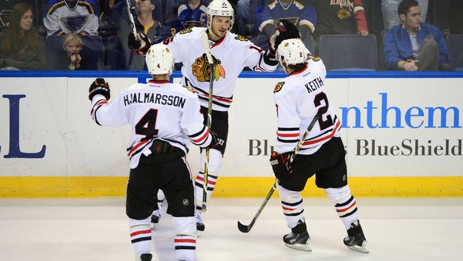 Chicago Blackhawks center Artem Anisimov (15) celebrates with defenseman Duncan Keith (2) and defenseman Niklas Hjalmarsson (4) after scoring an empty net goal against the St. Louis Blues during the third period at Scottrade Center.